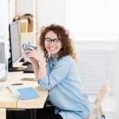 Smiling young woman at computer