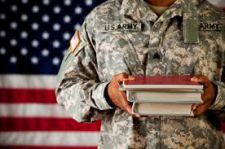 Military member holding textbooks standing in front of the American flag