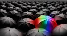 Rainbow colored umbrella in sea of black umbrellas