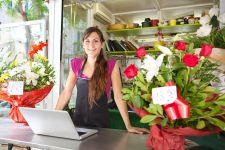 Smiling female florist standing behind counter of floral shop