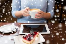 Woman holding coffee at laptop with snow falling