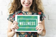 "Young female holding a ""wellness"" sign"