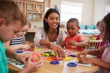 Smiling female daycare worker surrounded by young children