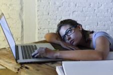 Exhausted female student at laptop